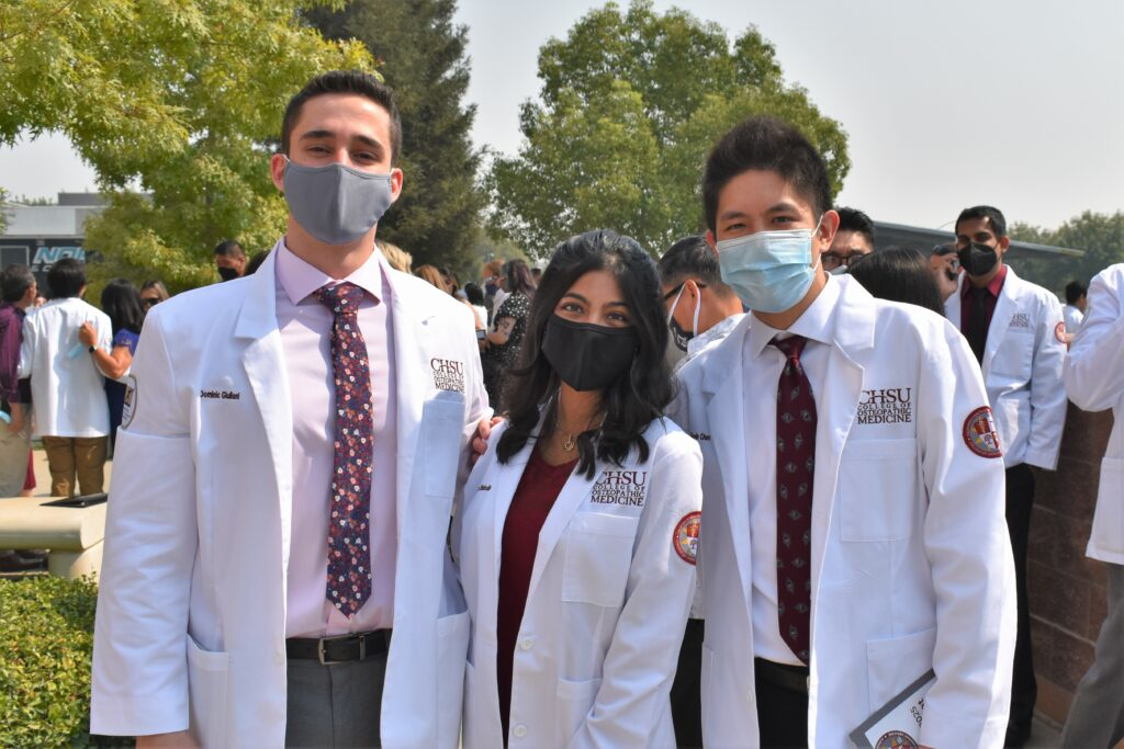 students posing in white coats